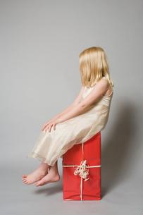 Girl sitting on a presentの写真素材 [FYI03461977]