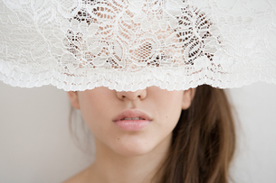 Woman behind a net curtainの写真素材 [FYI03462024]