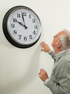 Senior man looking at a large clockの写真素材 [FYI03462091]
