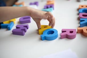 アルファベットの木のおもちゃで遊んでいる子供の手元の写真素材 [FYI03462253]