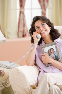 Woman calling with picture of familyの写真素材 [FYI03462306]