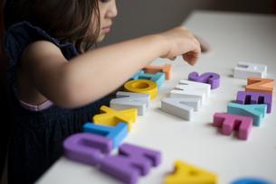 アルファベットの木のおもちゃで遊んでいる女の子の写真素材 [FYI03462599]