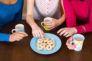 Three women having tea and biscuitsの写真素材 [FYI03462796]