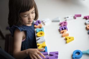 アルファベットの木のおもちゃで遊んでいる女の子の写真素材 [FYI03462888]