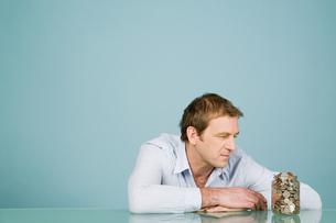 Man looking at jar of coinsの写真素材 [FYI03463236]