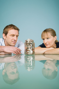 Couple looking at jar of coinsの写真素材 [FYI03463246]