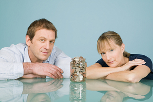 Couple with jar of coinsの写真素材 [FYI03463277]