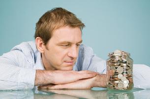 Man looking at jar of coinsの写真素材 [FYI03463289]