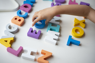 アルファベットの木のおもちゃで遊んでいる子供の手元の写真素材 [FYI03463453]