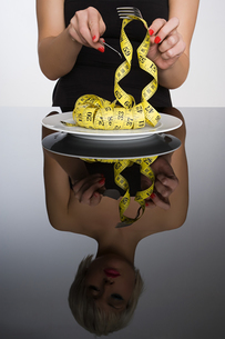 Woman eating a tape measureの写真素材 [FYI03463796]