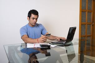 A man sorting his finances on a laptopの写真素材 [FYI03463876]