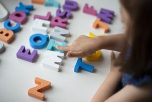 アルファベットの木のおもちゃで遊んでいる子供の写真素材 [FYI03463896]