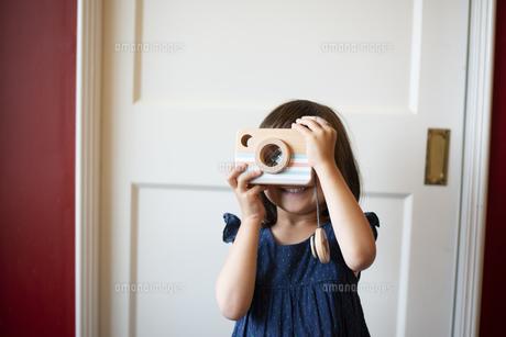 木のカメラのおもちゃで遊んでいる女の子の写真素材 [FYI03464472]