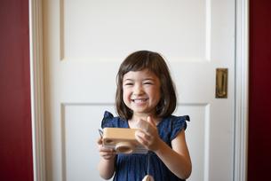 木のカメラのおもちゃで遊んでいる女の子の写真素材 [FYI03464907]