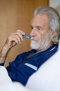 Man using thermometerの写真素材 [FYI03464912]