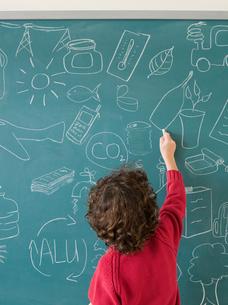 Boy writing on a blackboardの写真素材 [FYI03464963]