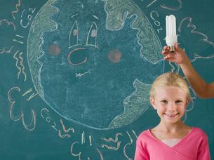 Girl with energy saving lightbulbの写真素材 [FYI03464993]