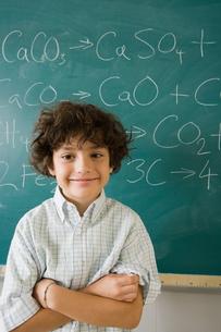 Boy standing by blackboardの写真素材 [FYI03465004]