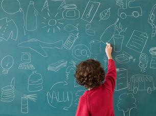 Boy drawing on a blackboardの写真素材 [FYI03465005]