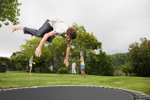 A boy doing somersaults on a trampolineの写真素材 [FYI03465214]