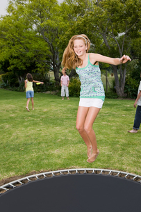A teenage girl jumping on a trampolineの写真素材 [FYI03465220]