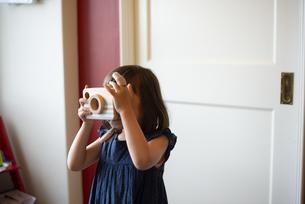 木のカメラのおもちゃで遊んでいる女の子の写真素材 [FYI03465262]