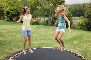 Teenage girls jumping on a trampolineの写真素材 [FYI03465265]