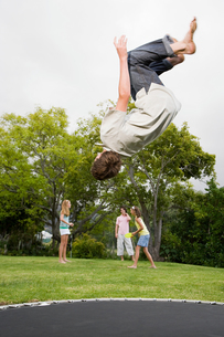 A boy doing somersaults on a trampolineの写真素材 [FYI03465284]