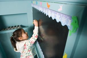 A girl writing on a blackboardの写真素材 [FYI03465323]