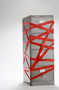 Red tape over filing cabinetの写真素材 [FYI03465918]
