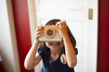 木のカメラのおもちゃで遊んでいる女の子の写真素材 [FYI03466445]