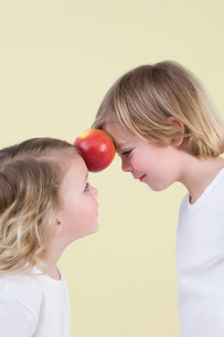 Boy and girl with apple between themの写真素材 [FYI03466527]