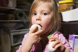 Girl trying to eat eggの写真素材 [FYI03467254]