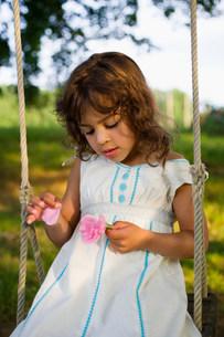 A girl picking petals off a flowerの写真素材 [FYI03467932]