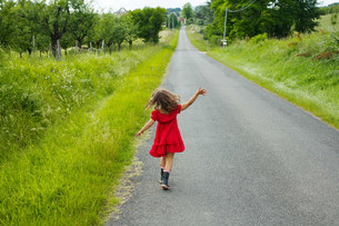 A girl skipping down a country roadの写真素材 [FYI03467933]