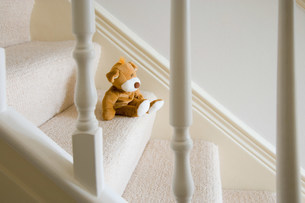 Soft toy on stairsの写真素材 [FYI03468196]