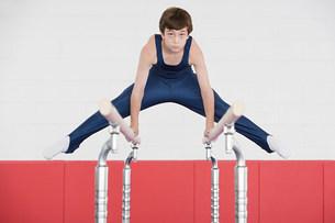 Gymnast doing the splits on parallel barsの写真素材 [FYI03468429]