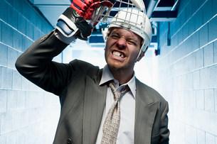 Grimacing businessman in a sports helmetの写真素材 [FYI03468612]