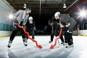 Businessmen playing ice hockeyの写真素材 [FYI03468615]