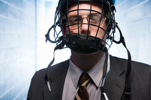 Injured businessman wearing an ice hockey helmetの写真素材 [FYI03468625]