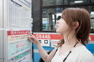 Young woman looking at bus timetableの写真素材 [FYI03468991]