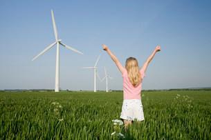 Girl in a field by wind farmの写真素材 [FYI03469018]