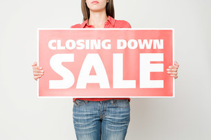 Woman holding a closing down signの写真素材 [FYI03469347]