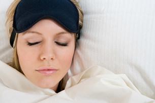 Sleeping woman wearing eye maskの写真素材 [FYI03469403]
