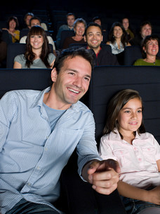 A father and daughter watching a movieの写真素材 [FYI03469418]