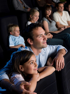 Father and daughter watching a movieの写真素材 [FYI03469440]