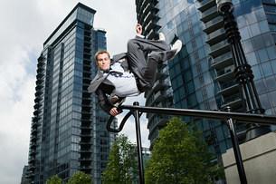 Businessman swinging on railingの写真素材 [FYI03469587]