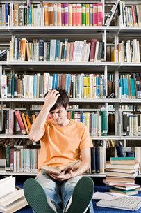 Confused student in libraryの写真素材 [FYI03469603]
