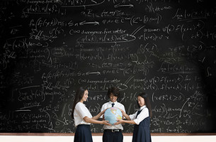 Students with globe in front of blackboardの写真素材 [FYI03469869]
