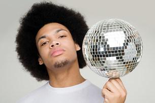 A young man balancing a disco ballの写真素材 [FYI03470100]